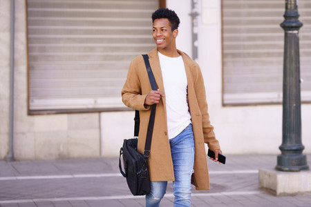 Smiling black man walking down the street carrying a briefcase and a smartphone in his hand