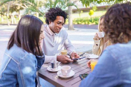 Black man showing his smartphone to his group of friends while having drinks at an outdoor bar