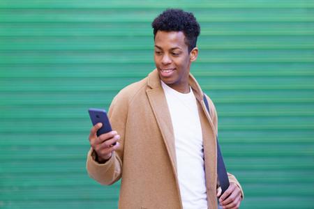 Cuban young man using a smartphone near a urban wall