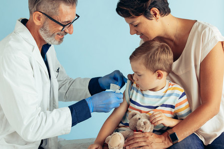 Boy getting vaccinated by doctor