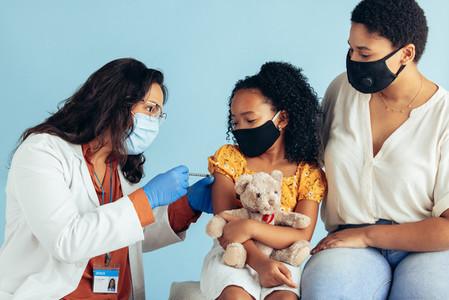 Doctor giving corona virus vaccine to a girl