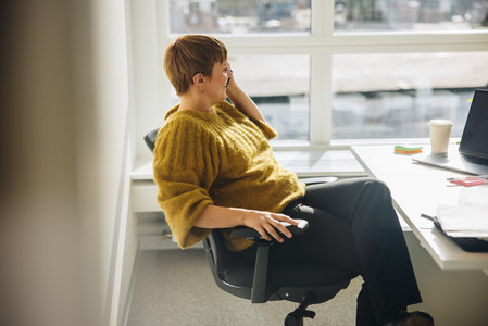 Female executive talking over phone sitting at her desk