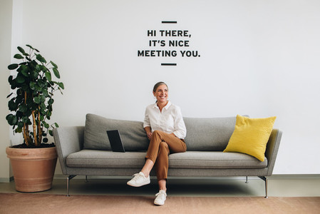 Happy female entrepreneur at office lobby