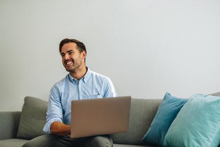 Happy freelancer man using laptop in lobby