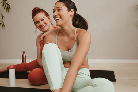 Smiling women friends relaxing after fitness training