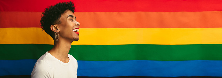 Transgender male smiling against pride flag