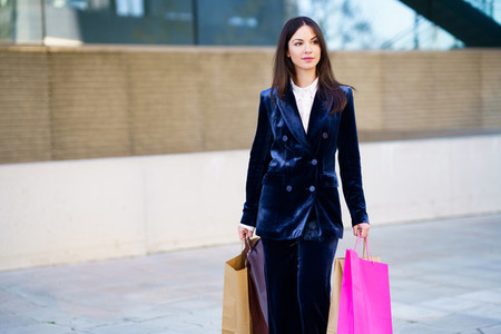 Young woman wearing blue suit carrying several shopping bags near a shopping mall
