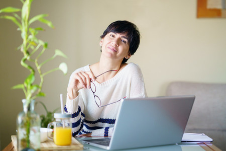 Smiling woman teleworking from home with her laptop