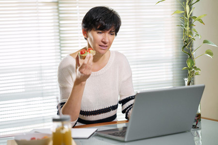 Woman eating some healthy food  while teleworking from home on her laptop