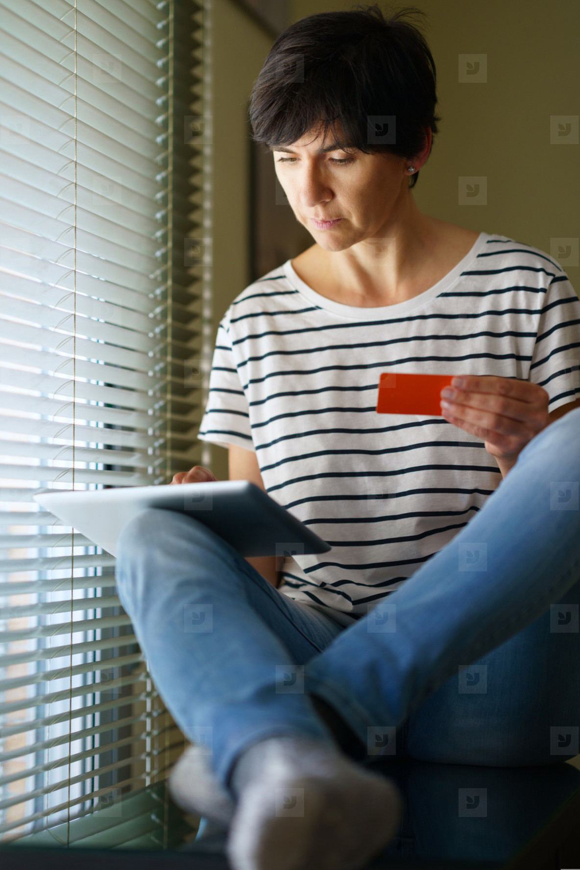 Middle aged woman shopping online with her digital tablet paying with a credit card