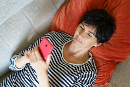 Woman checking Social Networks on her smartphone lying on the couch at home
