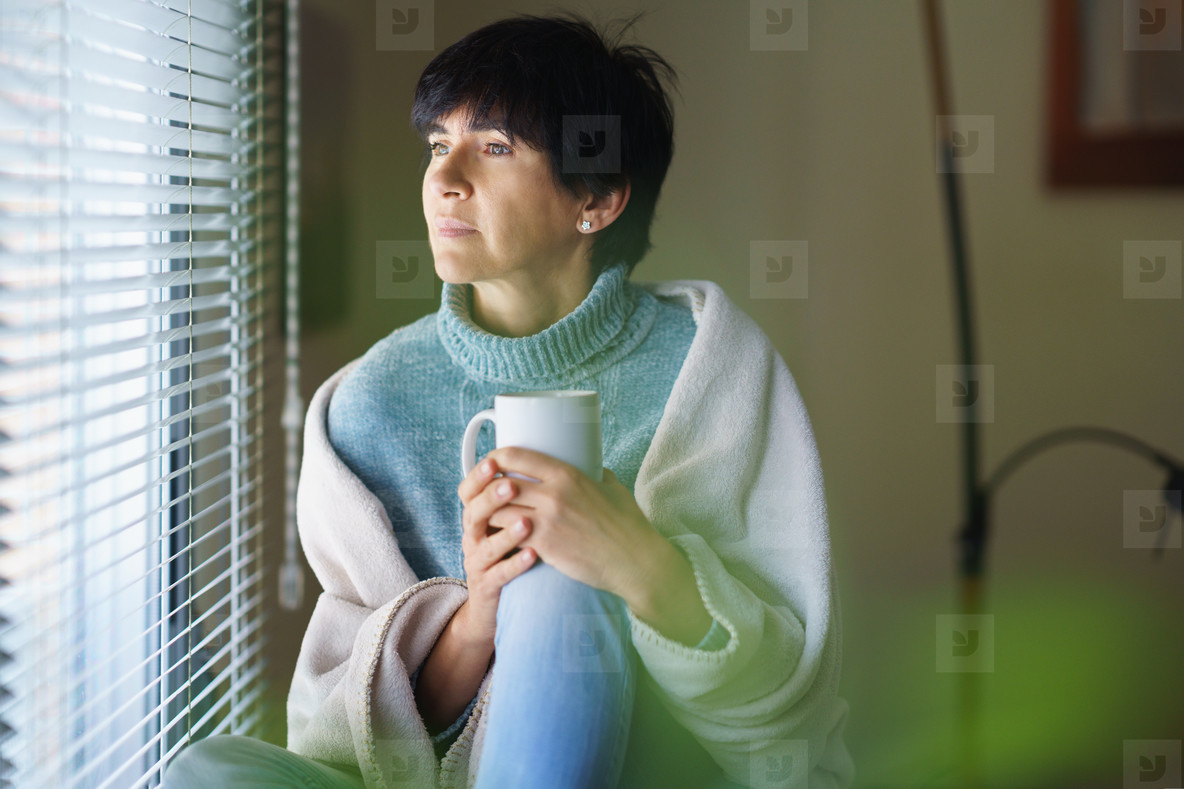 Mid adult woman drinking coffee and looking out of the window in winter day