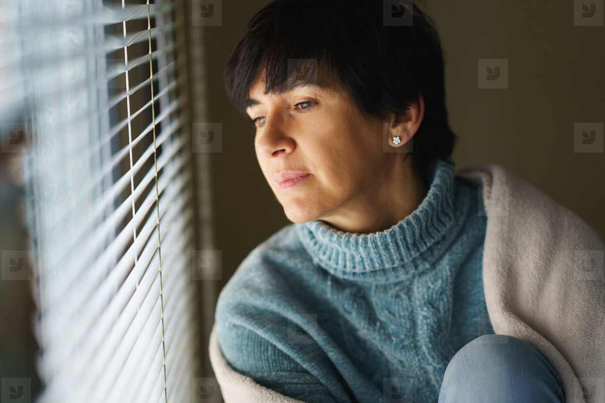 Happy middle aged woman with nostalgic look as she gazes out the window