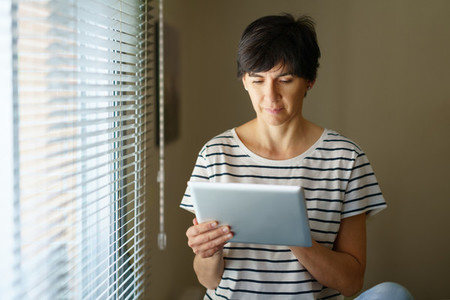 Middle aged woman consulting on her digital tablet sitting near the window at home