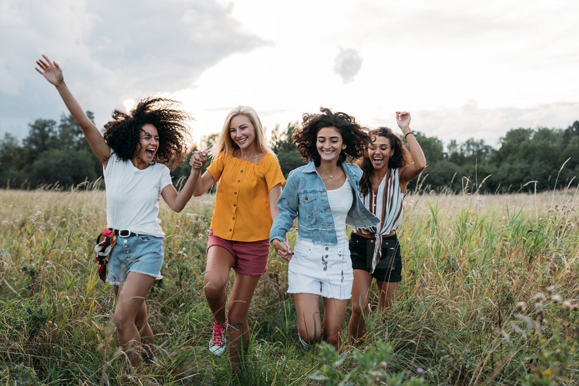 Four laughing women enjoying summer vacation  Happy friends running on the field