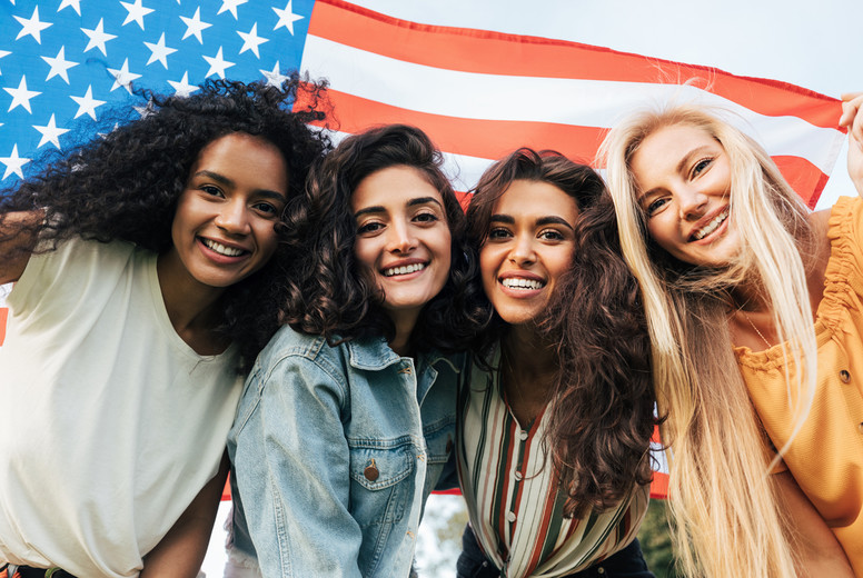 Four diverse women friends looking at the camera under the American flag  Cheerful females celebrating the 4th of July outdoors