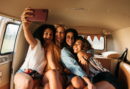 Four beautiful friends taking selfie in a van during a road trip  Smiling women on vacation