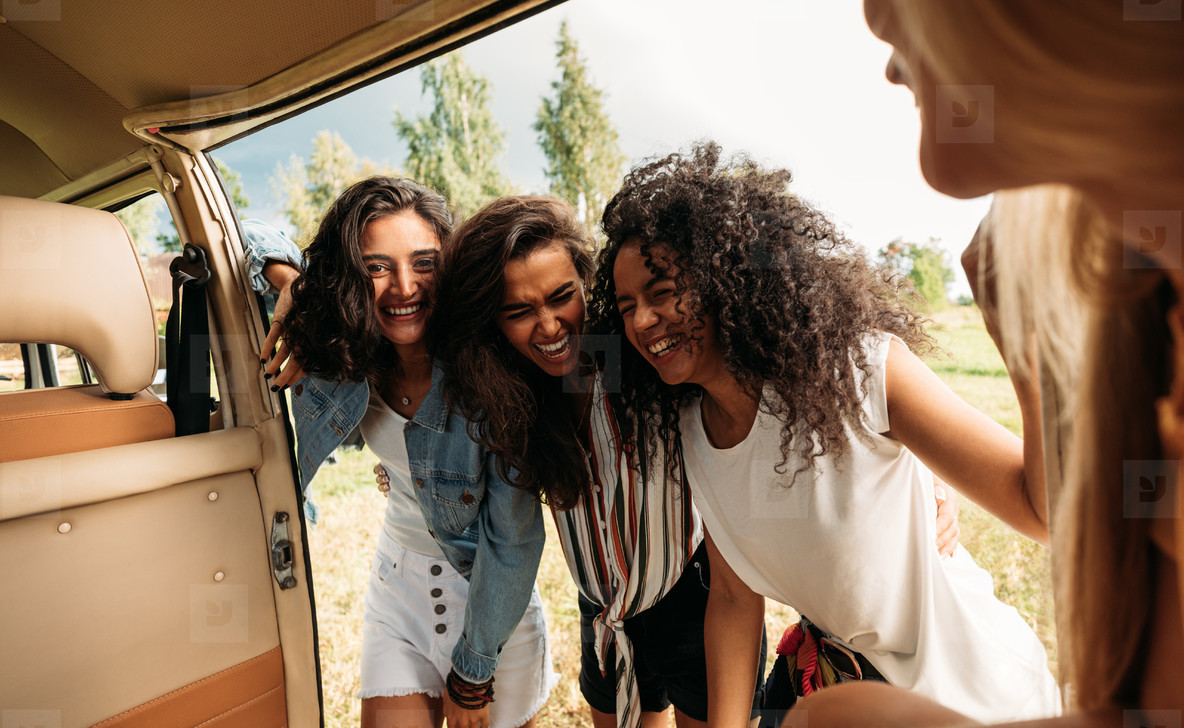 Group of friends on road trip laughing at van  Young people standing together and having fun at minivan door