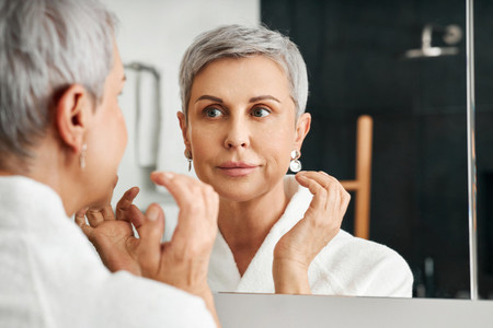 Smiling mature woman looking at her reflection while applying moisturizer on the face