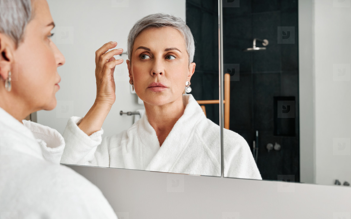 Mature woman adjusting her hairstyle in front of a mirror in bathroom