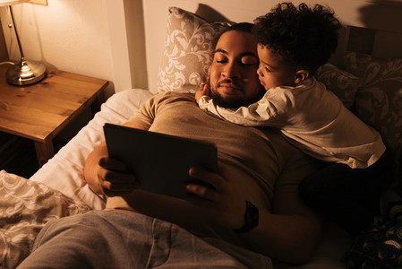 Little boy embracing his father while them lying on a bed  Young father reading book to his child from a digital tablet before sleeping