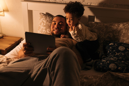 Smiling dad and his little son in bed watching content on a digital tablet