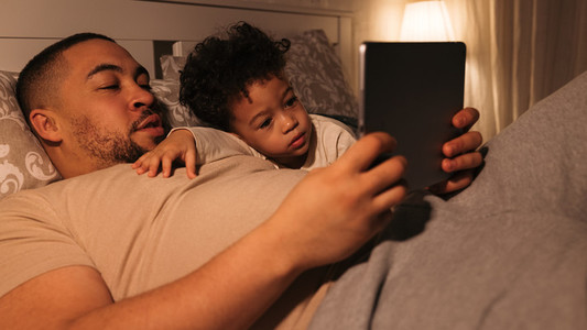 Close up view of man and boy lying on bed and reading book on digital tablet  Father and son looking on tablet pc at bedtime