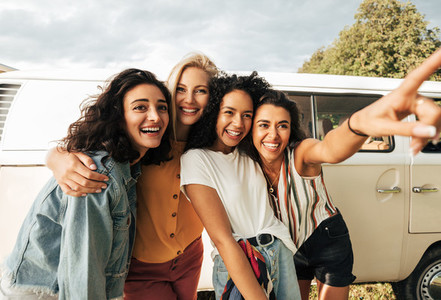 Group of young laughing women stopped during a road trip