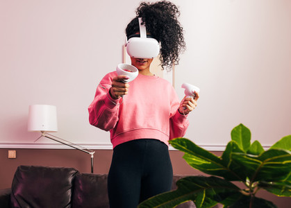 Woman in sweatshirt using a VR set while standing in living room