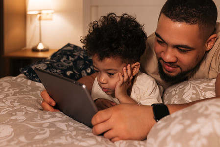 Young father and his son lying on a bed watching a movie on digital tablet at evening