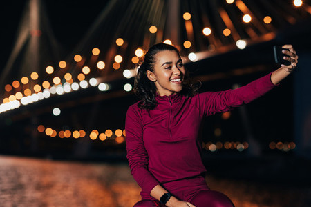Sportswoman sitting outdoors at night taking a selfie against city lights