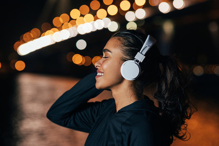 Side view of a fit woman in hooded shirt listening to music against night lights