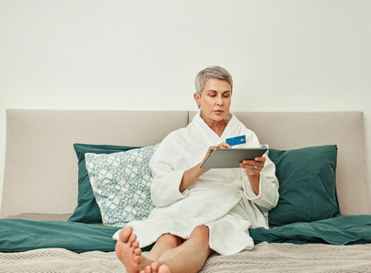 Senior woman with grey hair making an online purchase from bedroom