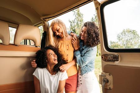 Three cheerful women having fun during road trip