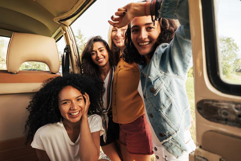 Four beautiful women looking at camera while sitting in minivan