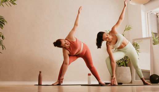 Two females practicing yoga at fitness studio