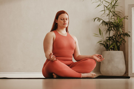 Woman meditating in fitness studio