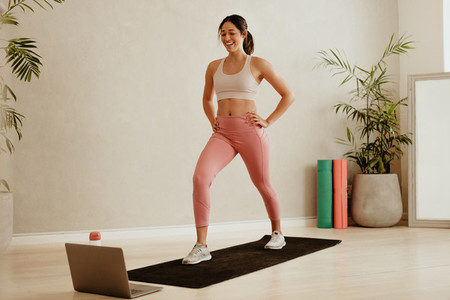 Woman fitness instructor teaching from studio virtually