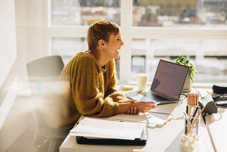 Smiling businessman sitting at her desk