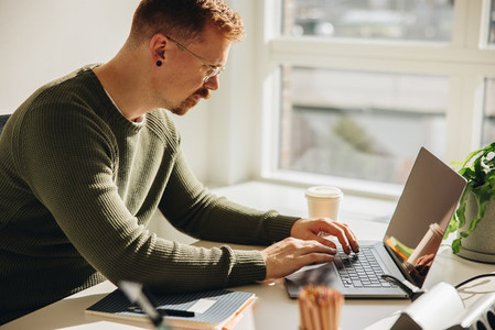 Male executive working on laptop in office
