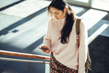 Female student in campus using mobile phone