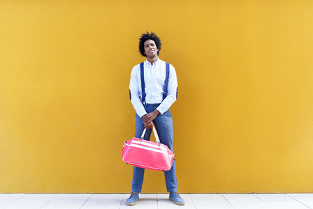 Black man with afro hairstyle carrying a sports bag on yellow background