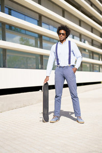 Black male worker standing next to an office building with a skateboard