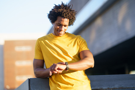 Black man consulting his smartwatch to view his training data