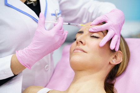 Aesthetic doctor injecting botox into the forehead of her middle aged patient