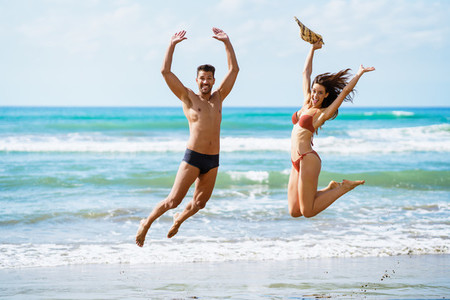 Funny young couple with beautiful bodies jumping on a tropical beach
