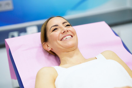 Middle aged woman lying on the stretcher in an aesthetic clinic