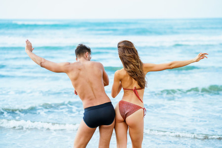 Young couple with beautiful bodies in swimwear having fun on a tropical beach