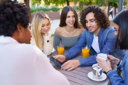 Guy showing his smartphone to his group of friends while having drinks at an outdoor bar