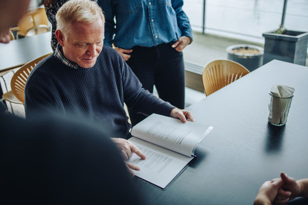 Businessman reading contract document for colleagues